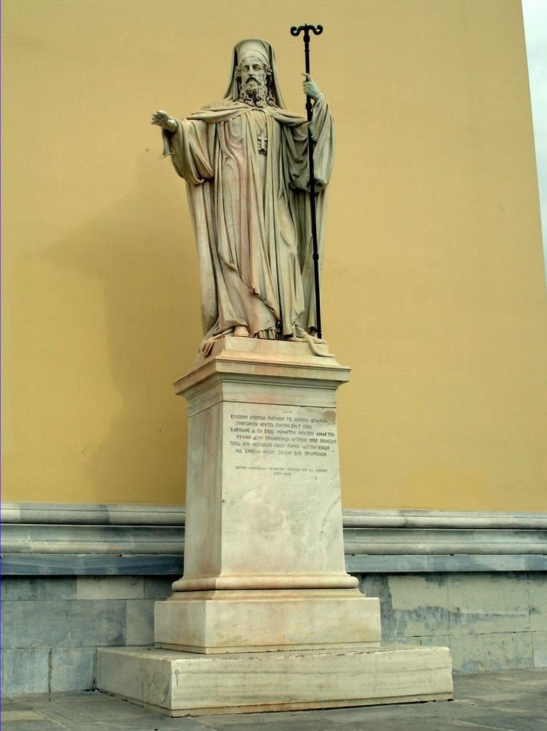 Ανδριάντας Πατριάρχου Γρηγορίου Ε΄ στο δεξιό μέρος της πρόσοψης του Πανεπιστημίου Αθηνών.