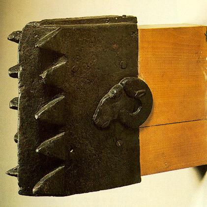 """Ο χάλκινος """"κριός"""" είναι η μοναδική στο είδος πολιορκητική μηχανή, που έχει διασωθεί από την αρχαιότητα. Έχει σχήμα ορθογωνίου παραλληλεπιπέδου. Η μία στενή πλευρά απολήγει σε μεγάλα δόντια και στην άλλη προσαρμοζόταν ο ξύλινος στειλεός, που δεν διατηρήθηκε. Σε κάθε πλατιά πλευρά του διακοσμείται με κεφαλή κριού. Στη διακόσμηση αυτή οφείλει και την ονομασία του. Τα δόντια είναι λυγισμένα και φθαρμένα, γεγονός που φανερώνει ότι είχε χρησιμοποιηθεί ως πολιορκητική μηχανή πριν αφιερωθεί στο ιερό του Δία της Ολυμπίας. Χρονολογείται στο πρώτο μισό του 5ου αι. π. Χ. και ίσως είναι σικελικού εργαστηρίου."""