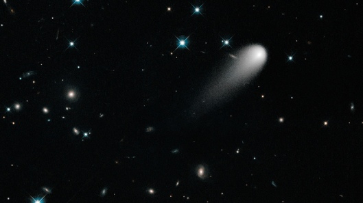 Comet ISON Comet ISON floats against a seemingly infinite backdrop of numerous galaxies and a handful of foreground stars. The icy visitor, with its long gossamer tail, appears to be swimming like a tadpole through a deep pond of celestial wonders. In reality, the comet is much, much closer. The nearest star to the Sun is over 60,000 times farther away, and the nearest large galaxy to the Milky Way is over thirty billion times more distant.