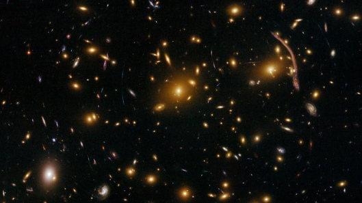 Abell 370 Abell 370 is one of the very first galaxy clusters where astronomers observed the phenomenon of gravitational lensing, where the warping of space by the cluster's gravitational field distorts and magnifies the light from galaxies lying far behind it. This is manifested as arcs and streaks in the picture, which are the stretched images of background galaxies