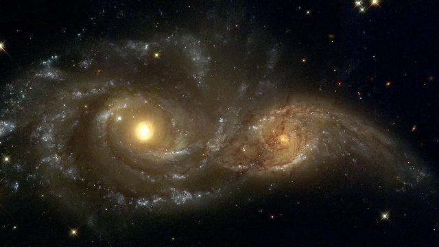 Interacting Galaxies NGC 2207 and IC 2163 Two spiral galaxies pass by each other like majestic ships in the night. The larger and more massive galaxy is cataloged as NGC 2207 (left), and the smaller one on the right is IC 2163. Strong tidal forces from NGC 2207 have distorted the shape of IC 2163, flinging out stars and gas into long streamers stretching out a hundred thousand light-years