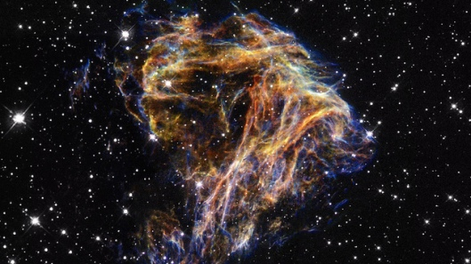 DEM L 190 Resembling the puffs of smoke and sparks from a summer fireworks display, these delicate filaments are actually sheets of debris from a stellar explosion in a neighboring galaxy. Denoted N 49, or DEM L 190, this is the remnant of a massive star that died in a supernova blast whose light would have reached Earth thousands of years ago.
