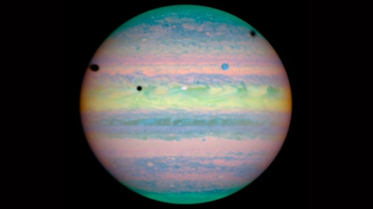 Triple Eclipse on Jupiter Scientist Pick: Five spots — one colored white, one blue, and three black — are scattered across the upper half of Jupiter. Closer inspection by Hubble reveals that these spots are actually a rare alignment of three of Jupiter's largest moons — Io, Ganymede, and Callisto — across the planet's face. Jupiter appears in pastel colors in this photo because the observation was taken in near-infrared light
