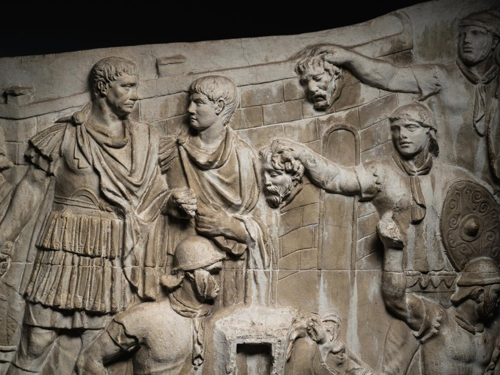 In a visual narrative that winds from the column's base to its top, Trajan and his soldiers triumph over the Dacians. In this scene from a plaster and marble-dust cast made between 1939 and 1943, Trajan (at far left) watches a battle, while two Roman auxiliaries present him with severed enemy heads. NATIONAL HISTORY MUSEUM OF ROMANIA