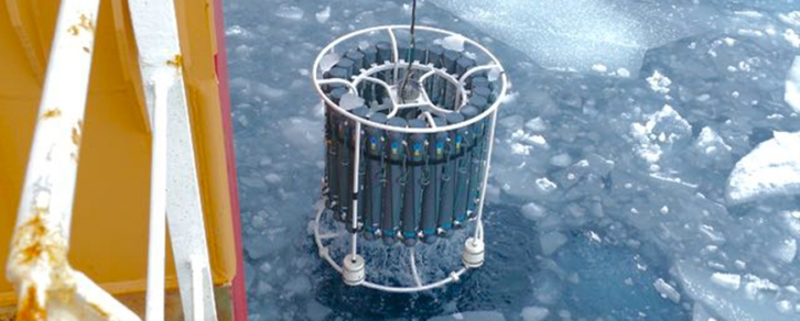 A rosette with seawater from various depths is retrieved from the Arctic Ocean by Coast Guard Cutter Healy.