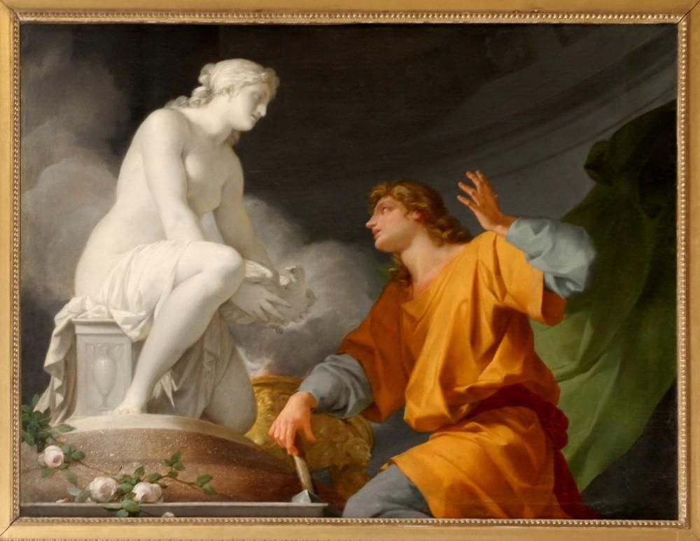 Αναφορά στο μύθο του Πυγμαλίωνα από τον Οβίδιο (Μεταμορφώσεις, βιβλίο Χ). Σύμφωνα με το Επίτομο Λεξικό Ελληνικής Μυθολογίας Χάρη Πάτση, ο Πυγμαλίων είναι μυθικός βασιλιάς της Κύπρου ο οποίος ερωτεύθηκε ένα γυναικείο άγαλμα της Αφροδίτης από ελεφαντόδοντο. Ζήτησε από την θεά να του χαρίσει μια αληθινή γυναίκα όμοια με το άγαλμα και μετά από λί-γο είδε με έκπληξή του ότι το άγαλμα ήταν πια μια ζωντανή γυναίκα, η Γαλάτεια. Εικόνα: Châ-teau de Versailles, salon des nobles, Pygmalion priant Vénus d' animer sa statue, Jean-Baptiste Regnault _wikipedia