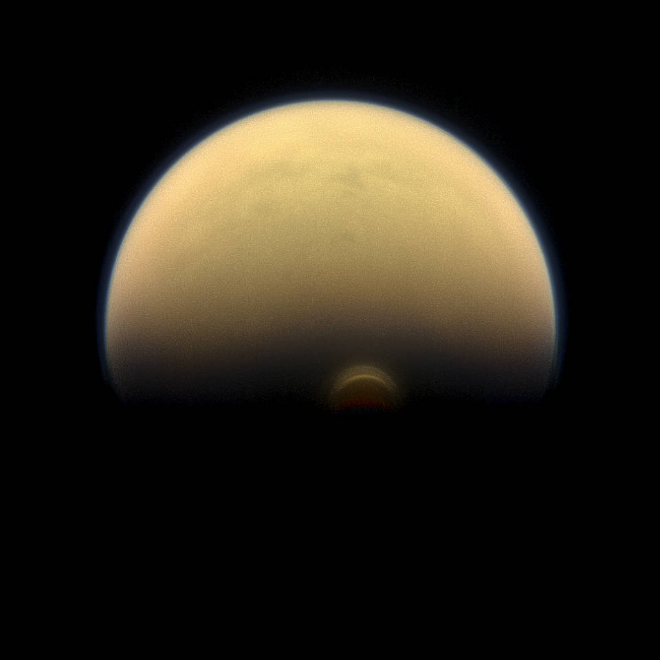 "As winter sets in at Titan's south pole, a cloud system called the south polar vortex (small, bright ""button"") has been forming, as seen in this 2013 image. Credits: NASA/JPL-Caltech/Space Science Institute"