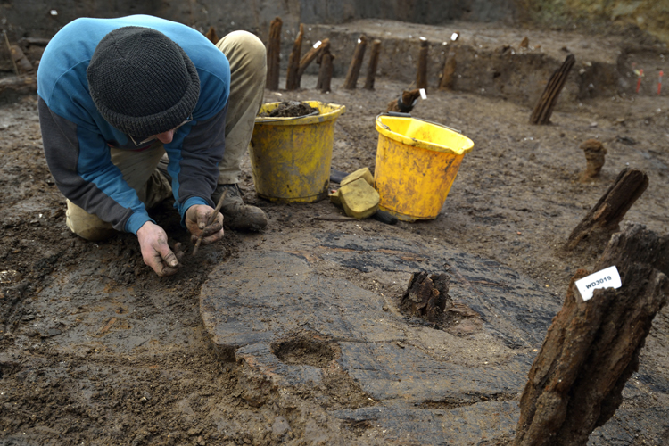 Excavation of Bronze Age Wheel at Must Farm one metre in diameter, with hub clearly visible. Copyright Cambridge Archaeological Unit, photo by Dave Webb