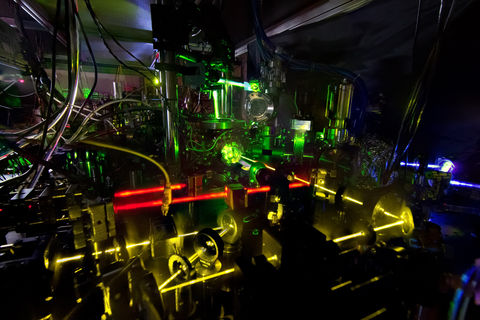 One of NIST's ytterbium lattice atomic clocks. NIST physicists combined two of these experimental clocks to make the world's most stable single atomic clock. The image is a stacked composite of about 10 photos in which an index card was positioned in front of the lasers to reveal the laser beam paths. Credit: N. Phillips/NIST